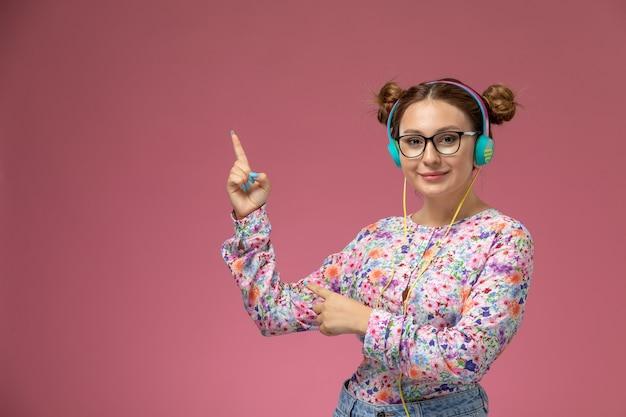 Vue de face jeune femme en chemise conçue de fleurs et blue-jeans, écouter de la musique avec le sourire sur le fond rose
