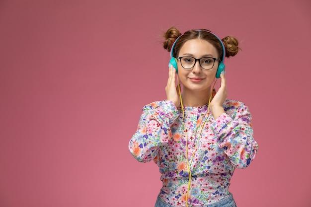 Vue de face jeune femme en chemise conçue de fleurs et blue-jeans, écouter de la musique avec le sourire sur son visage sur fond rose