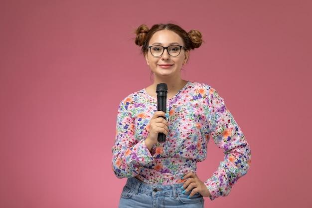 Vue de face jeune femme en chemise conçue de fleurs et blue-jeans essayant de chanter avec microphone sur fond rose