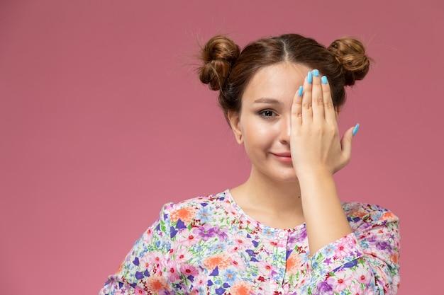 Vue de face jeune femme en chemise conçue de fleurs et blue-jeans souriant et couvrant son visage sur le fond rose