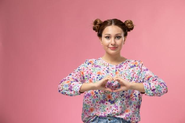 Vue de face jeune femme en chemise conçue de fleurs et jean bleu montrant signe de coeur souriant sur fond rose