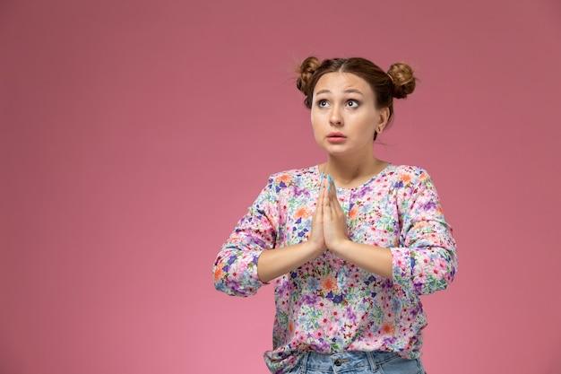 Vue de face jeune femme en chemise conçue de fleurs et jean bleu posant en prière pose sur le fond rose