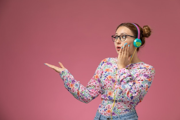 Vue de face jeune femme en chemise conçue de fleurs et jeans bleus, écouter de la musique avec des écouteurs sur le fond rose pose de modélisation femme