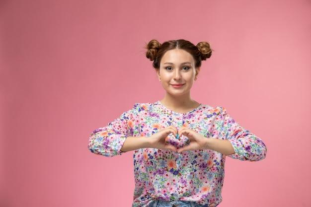 Vue de face jeune femme en chemise conçue de fleurs souriant montrant signe de coeur sur le fond rose