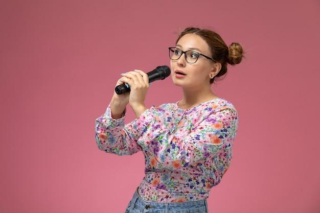 Vue de face jeune femme en chemise conçue de fleurs tenant un microphone chantant sur le fond rose