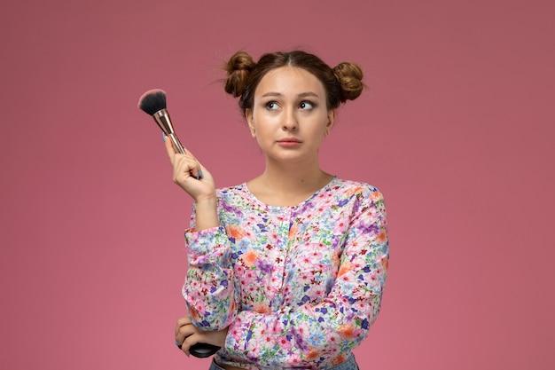 Vue de face jeune femme en chemise conçue de fleurs tenant un pinceau de maquillage pensant sur le fond rose