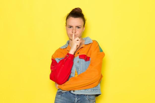 Une vue de face jeune femme en chemise jaune veste colorée et jean bleu
