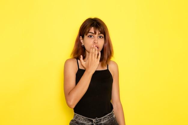 Vue de face de la jeune femme en chemise noire et jeans gris posant sur mur jaune