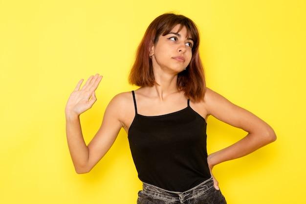 Vue de face de la jeune femme en chemise noire et jeans gris posant simplement sur le mur jaune