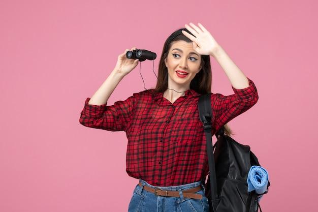 Vue de face jeune femme en chemise rouge à l'aide de jumelles sur fond rose couleur étudiant femme