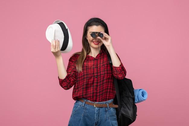 Vue de face jeune femme en chemise rouge à l'aide de jumelles sur le fond rose couleur femme humaine