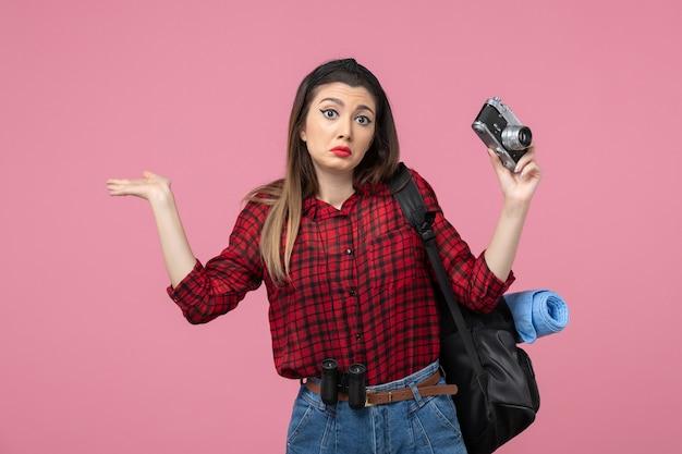 Vue de face jeune femme en chemise rouge avec appareil photo sur le modèle de femme photo fond rose