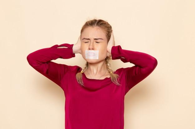 Vue de face jeune femme en chemise rouge avec bouche attachée oreilles collées sur l'espace crème femme tissu photo violence domestique
