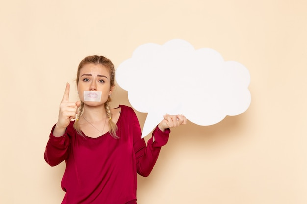 Vue de face jeune femme en chemise rouge avec bouche attachée pleurer tenant une pancarte blanche sur la violence de tissu féminin espace crème