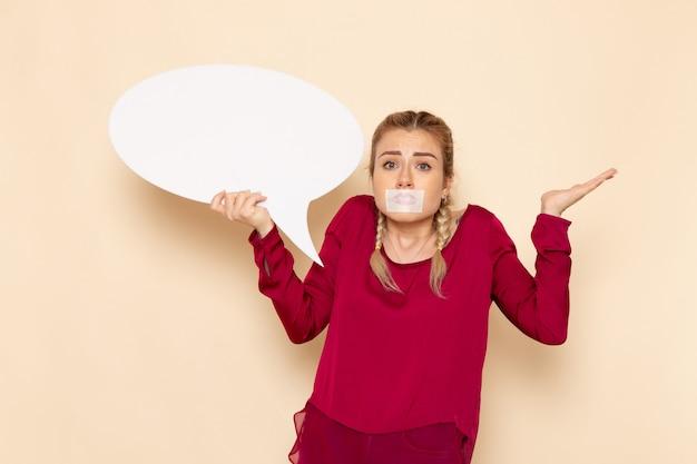 Vue de face jeune femme en chemise rouge avec bouche attachée tenant un énorme signe blanc sur l'espace crème femme tissu photo violence domestique