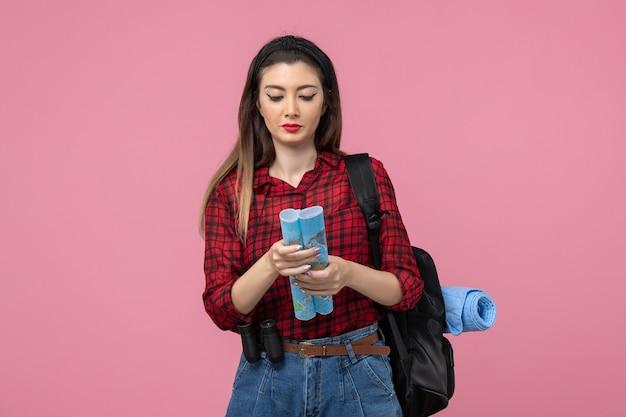 Vue de face jeune femme en chemise rouge avec carte sur fond rose clair femme mode couleur