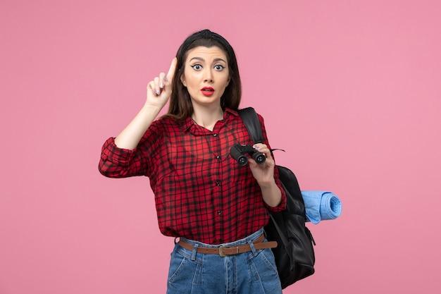 Vue de face jeune femme en chemise rouge avec des jumelles sur le bureau rose étudiant couleur femme