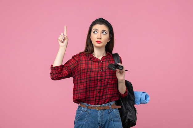 Vue de face jeune femme en chemise rouge avec des jumelles sur l'étudiant couleur fond rose femme
