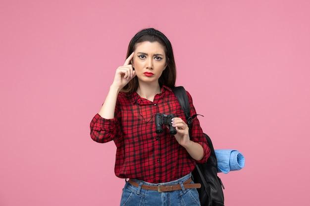 Vue de face jeune femme en chemise rouge avec des jumelles sur la femme de couleur étudiant fond rose