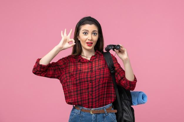 Vue de face jeune femme en chemise rouge avec des jumelles sur la femme de couleur mode fond rose