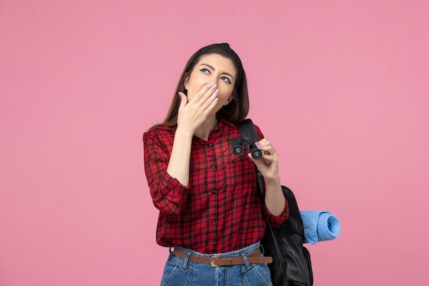 Vue de face jeune femme en chemise rouge avec des jumelles sur fond rose clair couleur mode femme