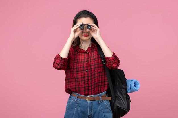 Vue de face jeune femme en chemise rouge avec des jumelles sur fond rose clair femme couleur étudiant