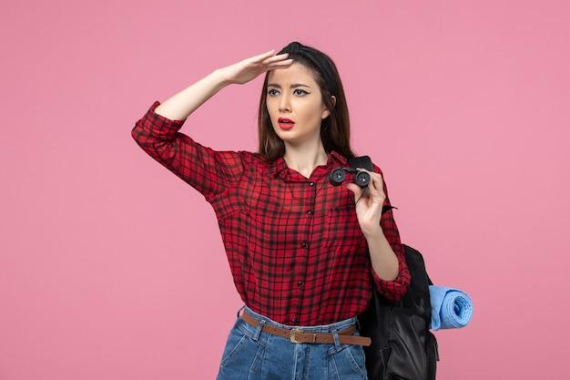Vue de face jeune femme en chemise rouge avec des jumelles sur fond rose couleur femme étudiante