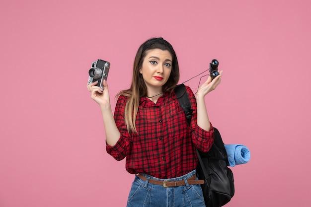 Vue de face jeune femme en chemise rouge avec des jumelles sur un fond rose femme de couleur humaine
