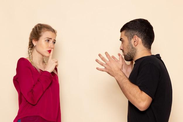 Vue de face jeune femme en chemise rouge souffre de violence verbale sur le tissu féminin espace crème