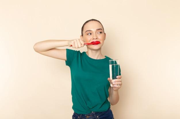 Vue de face jeune femme en chemise vert foncé et jean bleu nettoyant ses dents sur beige