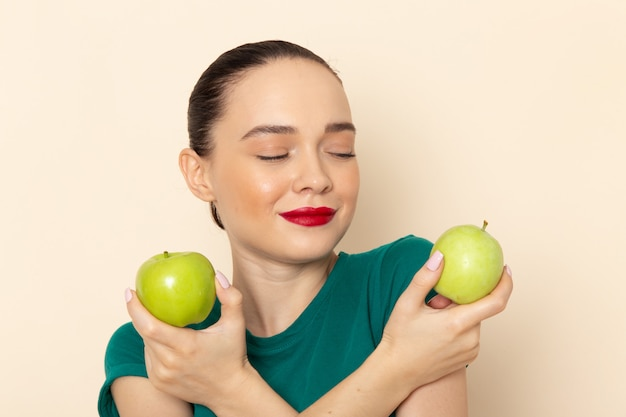 Vue de face jeune femme en chemise vert foncé et jean bleu tenant des pommes vertes avec sourire sur beige