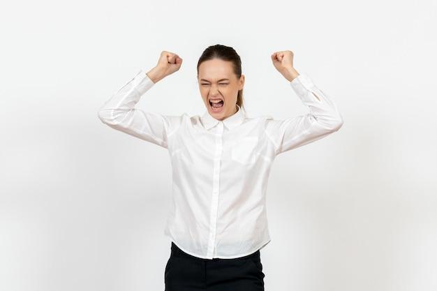 Vue de face jeune femme en chemisier blanc en colère jetant des fichiers sur fond blanc émotions féminines sentiments travail de bureau