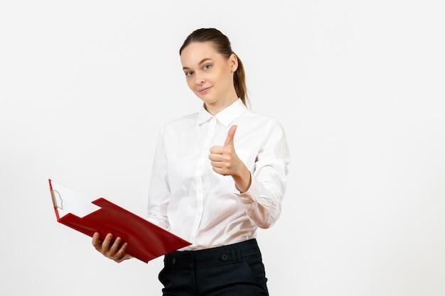 Vue de face jeune femme en chemisier blanc avec dossier rouge sur le bureau au sol blanc émotion féminine sentiment travail modèle