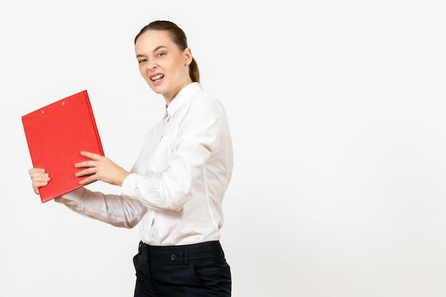 Vue de face jeune femme en chemisier blanc avec dossier rouge sur fond blanc bureau femme émotions sentiments modèle travail