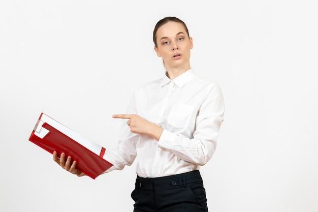 Vue de face jeune femme en chemisier blanc avec dossier rouge sur fond blanc bureau sentiment féminin émotion travail modèle