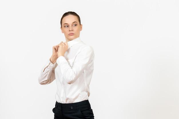 Vue de face jeune femme en chemisier blanc juste debout sur fond blanc bureau sentiment féminin émotion travail modèle