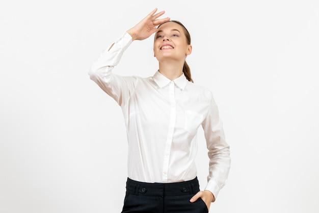 Vue de face jeune femme en chemisier blanc regardant à distance sur fond blanc bureau sentiment féminin émotion travail modèle