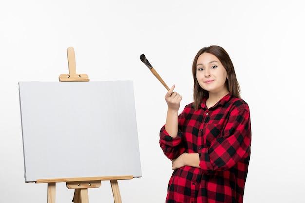 Vue de face jeune femme avec chevalet et pinceau sur mur blanc