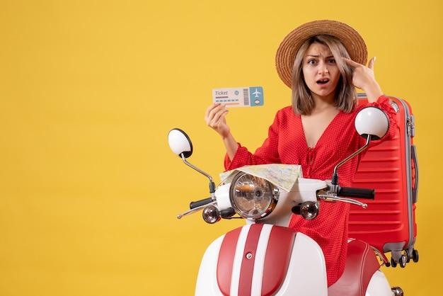 Vue de face de la jeune femme confuse en robe rouge holding ticket mettant le doigt sur sa tempe sur cyclomoteur