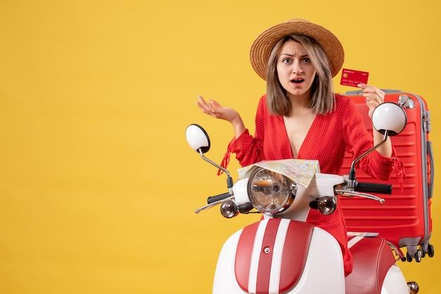 Vue de face d'une jeune femme confuse en robe rouge tenant une carte près de cyclomoteur