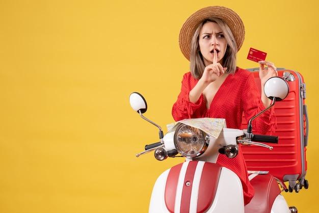 Vue de face jeune femme confuse tenant une carte de crédit près d'un cyclomoteur
