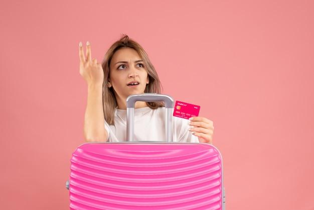 Vue de face de la jeune femme confuse tenant la carte derrière la valise