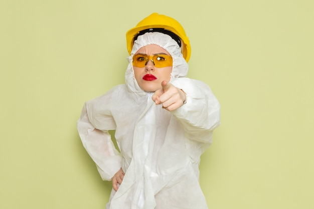 Vue de face jeune femme en costume spécial blanc et casque jaune menaçant sur l'emploi de l'espace vert