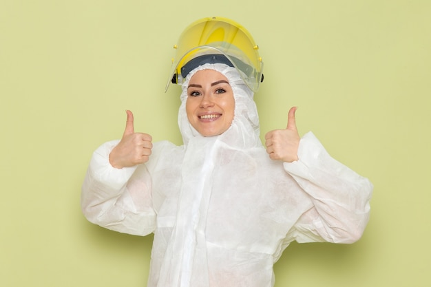 Vue de face jeune femme en costume spécial blanc et casque jaune posant avec le sourire sur le travail scientifique uniforme de combinaison d'espace vert