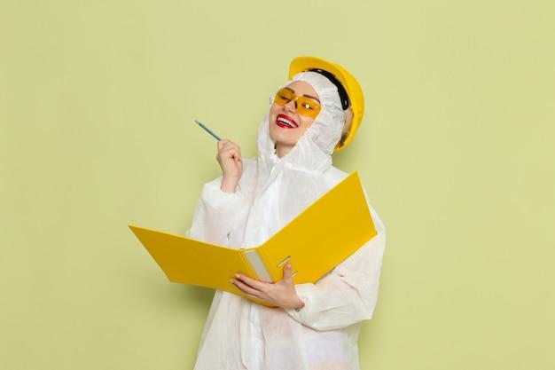 Vue de face jeune femme en costume spécial blanc et casque jaune tenant des fichiers jaunes et écrivant sur la science uniforme du costume d'espace vert