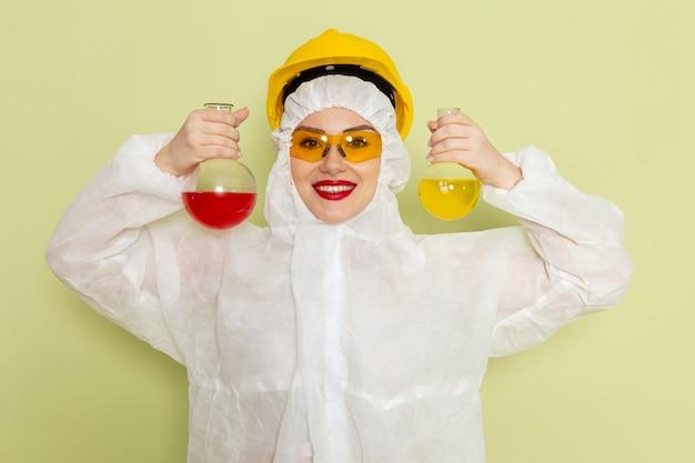 Vue de face jeune femme en costume spécial blanc et casque jaune tenant des flacons avec des solutions sur l'espace vert