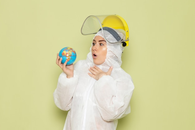 Vue de face jeune femme en costume spécial blanc et casque jaune tenant petit globe rond sur l'espace vert