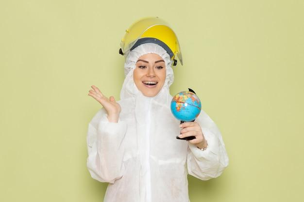 Vue de face jeune femme en costume spécial blanc et casque jaune tenant petit globe rond souriant sur le travail de chimie de l'espace vert s