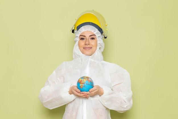 Vue de face jeune femme en costume spécial blanc et casque de protection jaune tenant petit globe rond avec un léger sourire sur l'espace vert