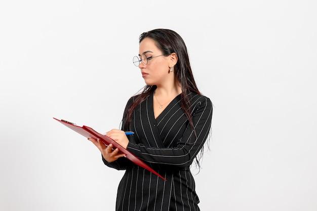 Vue de face jeune femme en costume strict foncé tenant un fichier rouge sur fond blanc bureau affaires travail mode document féminin